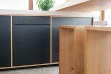 Metall trifft Massivholz: Schiebetüren aus schwarzem Lochblech, Hocker aus massiver Eiche.